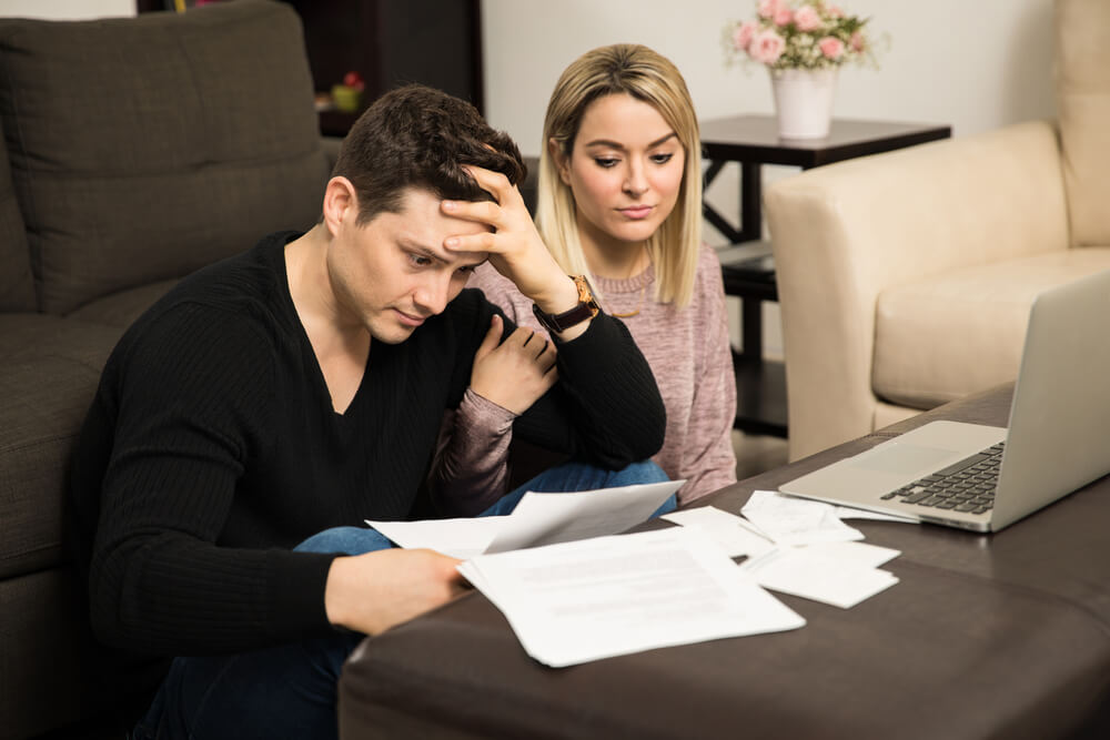 Young couple looking stressed and overwhelmed in front of a bunch of unpaid bills