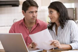 Husband and Wife Reviewing Car Insurance Bill