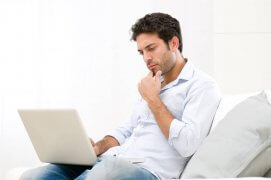 Young man looking at his laptop with pensive expression