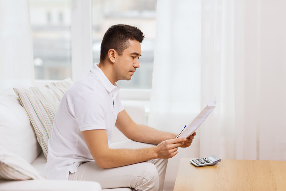 Man sitting on couch looking at car insurance bill