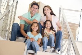 Family sitting on staircase with boxes in new apartment smiling