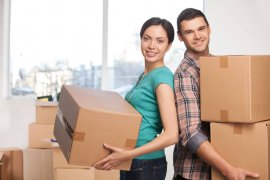 Young couple smiling moving boxes into new apartment
