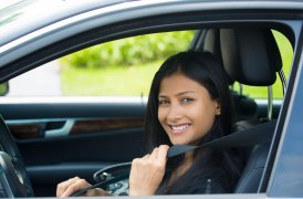 Photo of young smiling woman inside car putting on seatbelt.