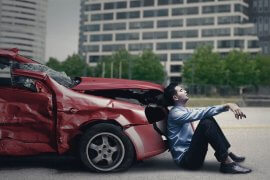 Image of stressed man sitting in front of a dented car after traffic accident