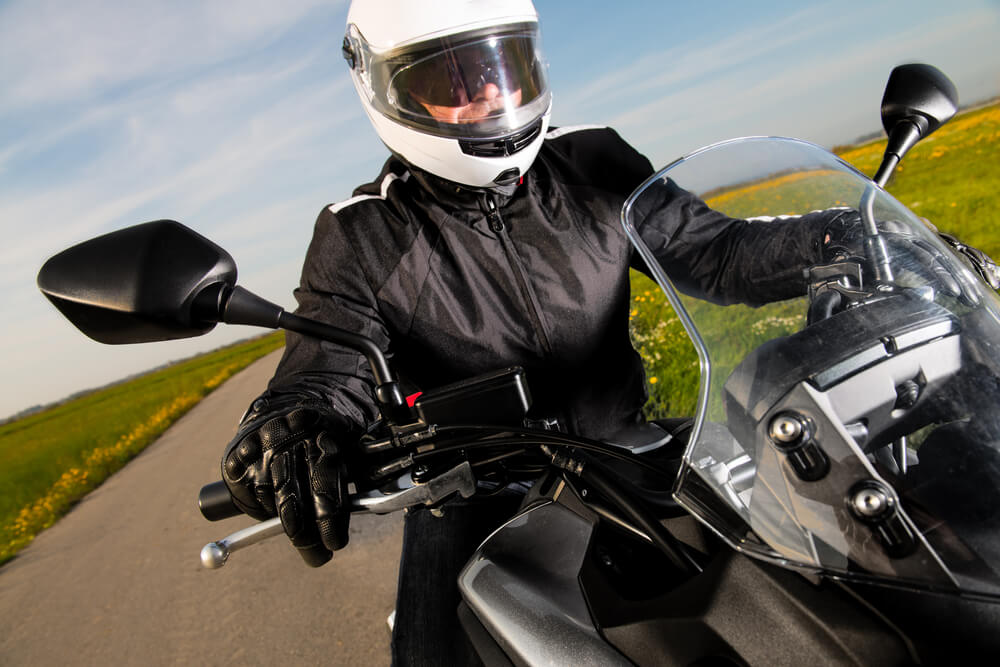 Biker in helmet and leather jacket riding a motorcyle on the road