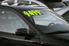 Auto for sale displaying price sticker on window in a used car lot