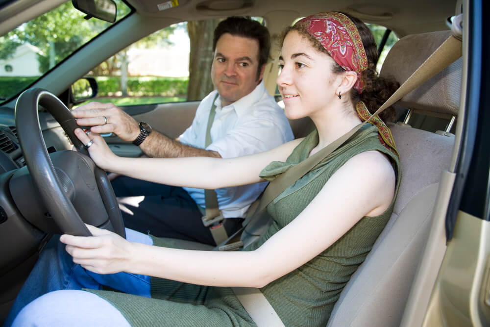 Teen girl taking driving lessons from her father