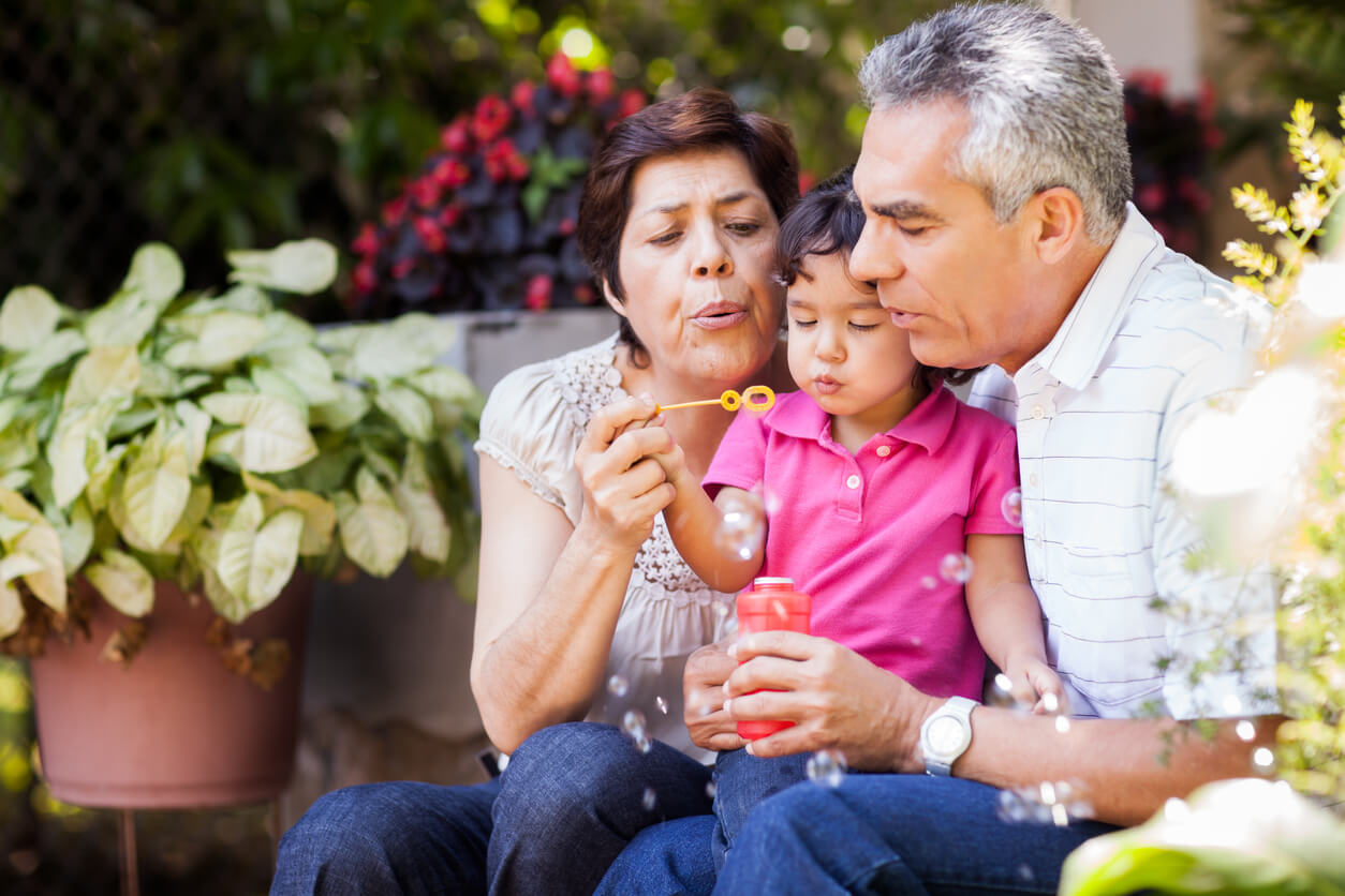 Older couple sitting in garden with granddaughter blowing bubbles