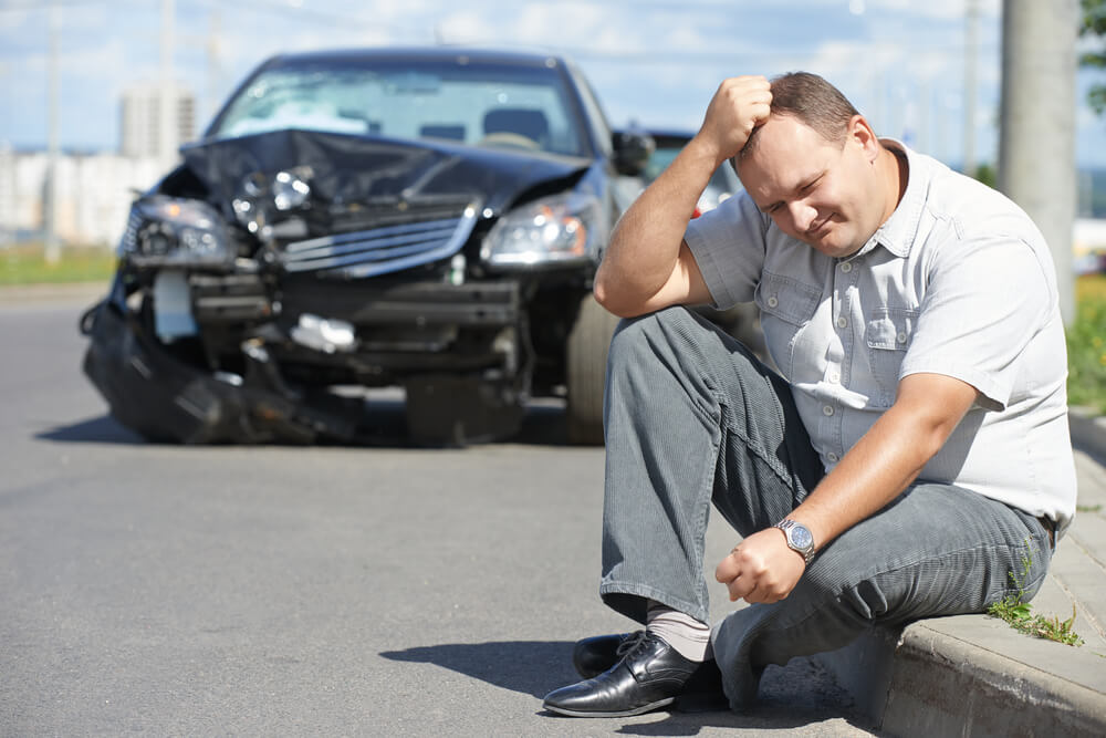 Upset male sitting on the ground in front of totaled car