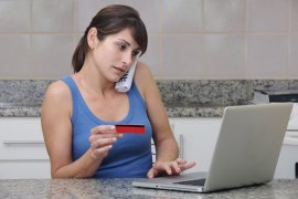 Concerned woman at home looking at laptop and holding credit card, victim of identity theft