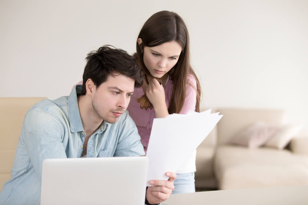 Young couple sitting in front of laptop looking at papers confused