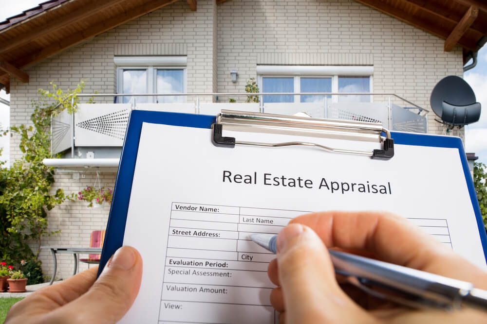Close up of hand filling out real estate appraisal form standing in front of house