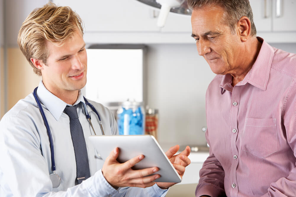 Doctor Discussing Health Records With Patient Using Digital Tablet