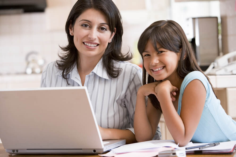 Woman and young girl in kitchen with laptop and health insurance forms smiling