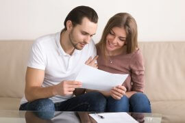Young couple sitting on couch in new apartment looking at renters insurance policy