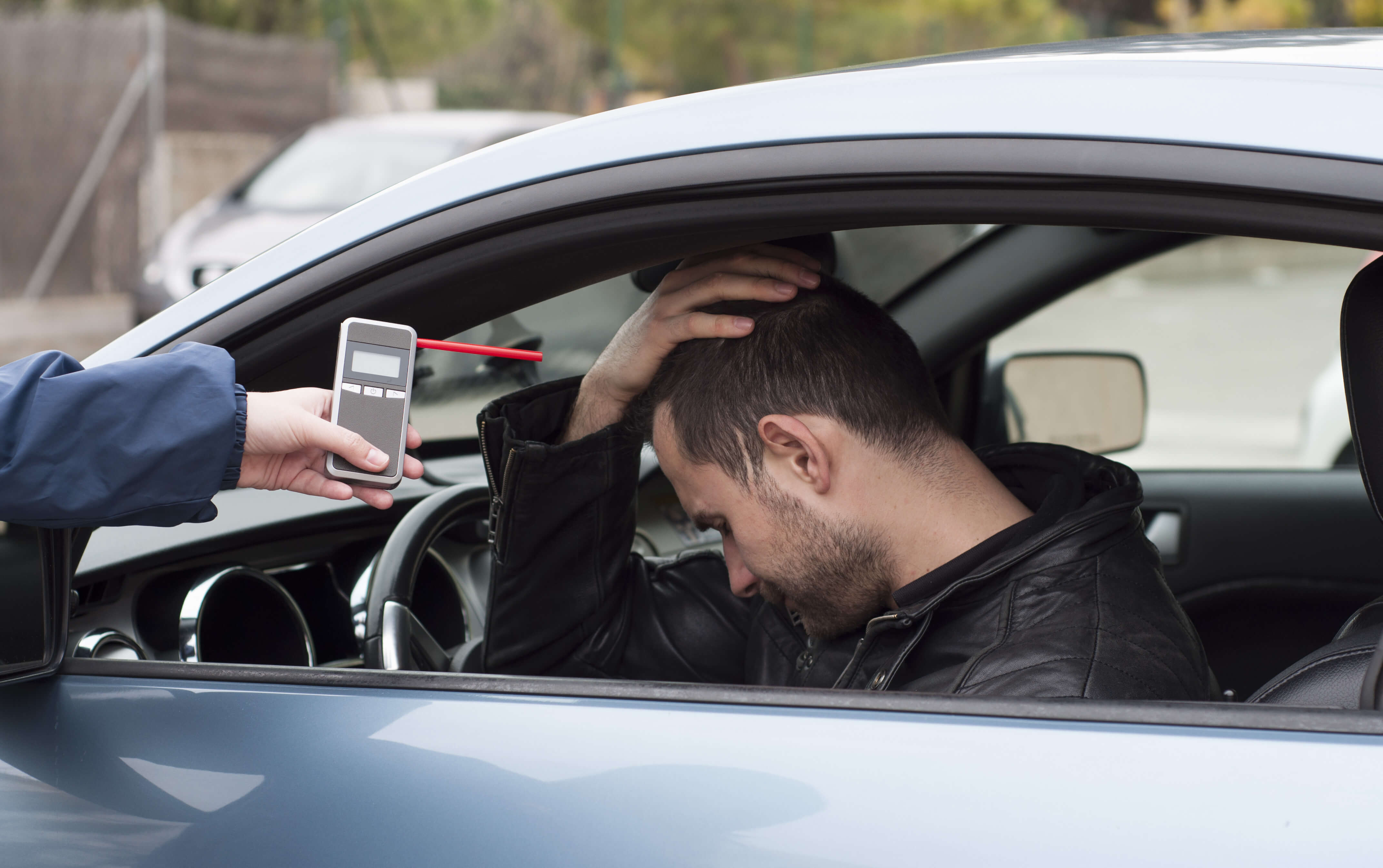 Drunk male driver behind the wheel of car being presented with breathalyzer device by police officer