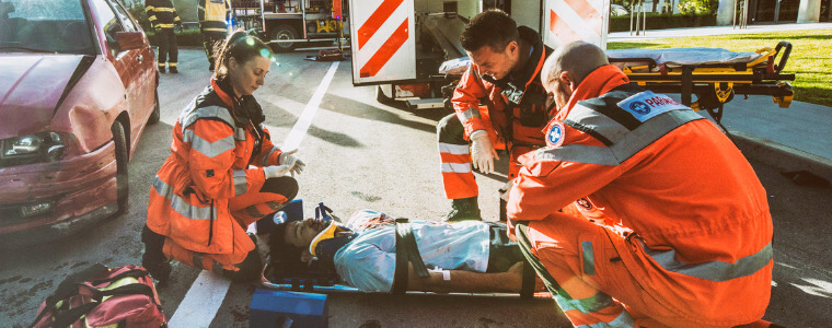 Young injured male lying on stretcher surround by paramedics with ambulence and crashed car in the background - Accidental Death and Dismemberment