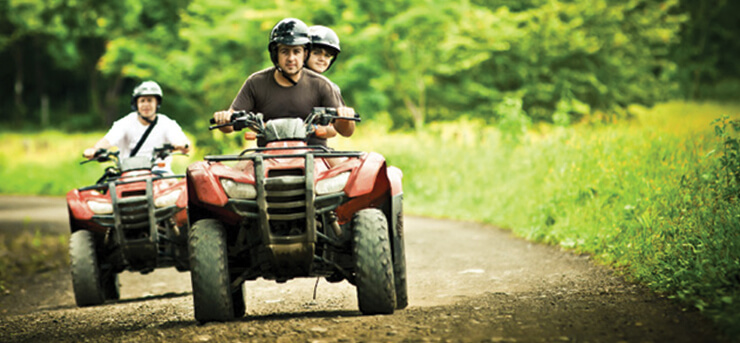 family on ATVs down a dirt road with ATV insurance