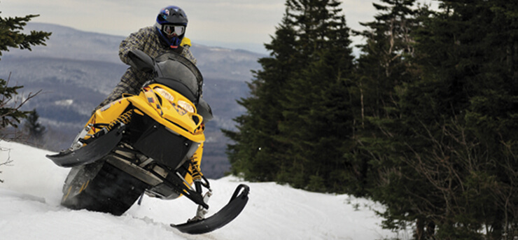 man riding a snowmobile on a slope with snowmobile insurance