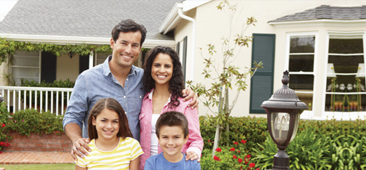 happy family in front of their home with homeowners insurance