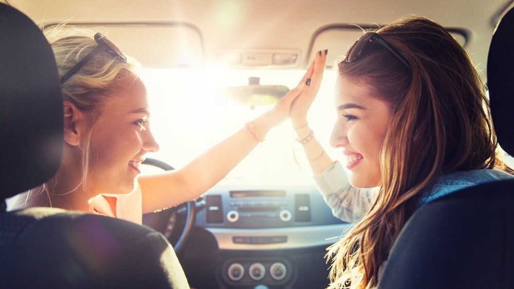 two female friends high five on a car one is a first time driver