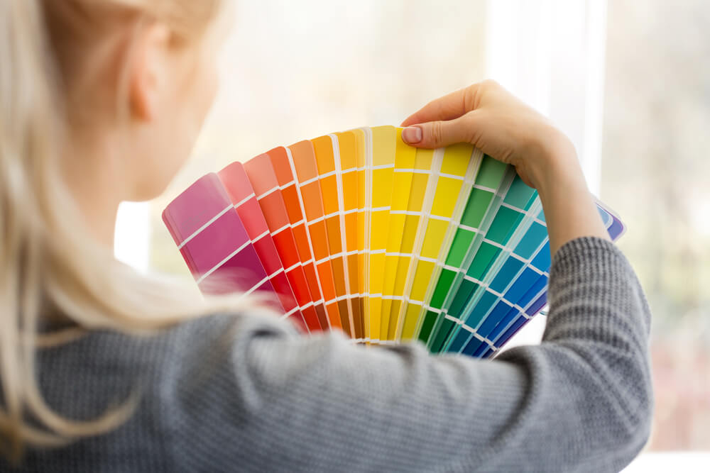 woman looking at paint swatch decor diy