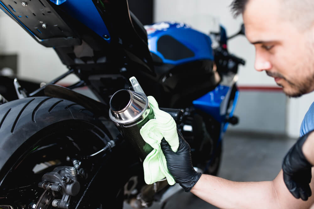 man cleaning his motorcycle for maintance